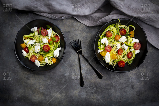 Directly above shot of vegetable salad served in bowls with forks by napkin on table