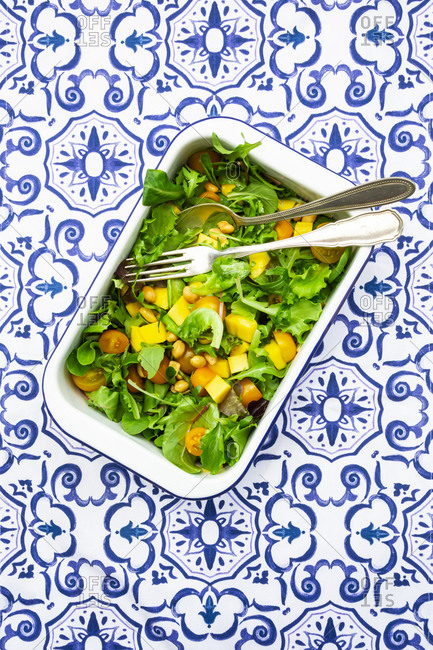 Directly above shot of vegetable salad with cutleries in bowl on patterned table