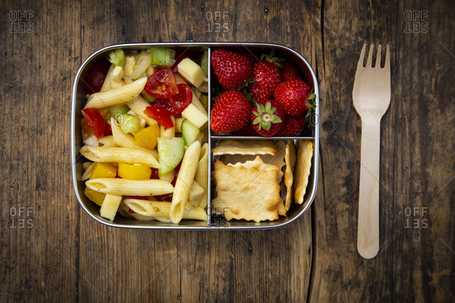 Directly above shot of pasta with strawberries and crackers in lunch box on wooden table