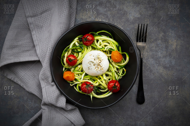 Bowl of zoodles with baked tomatoes and burrata cheese
