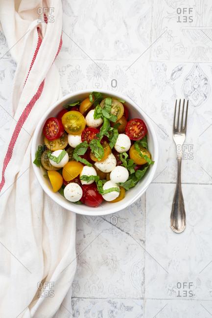 Napkin- single fork and bowl of fresh salad lying on tiled table