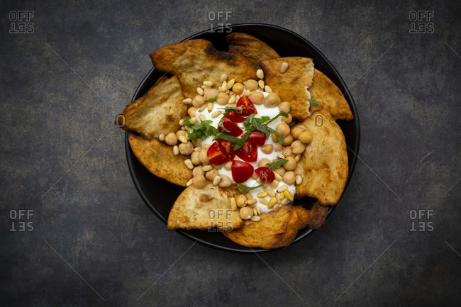 Bowl of Levantine fatteh- with flat bread- tomatoes and chickpeas
