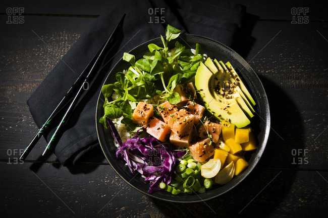 Directly above shot of poke bowl with chopsticks on wooden table