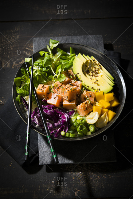 High angle view of poke bowl with chopsticks on wooden table