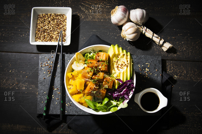 High angle view of poke bowl on wooden table