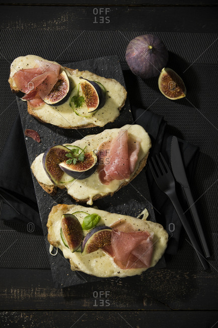 High angle view of baked cheese bread with fig slices and ham served on table