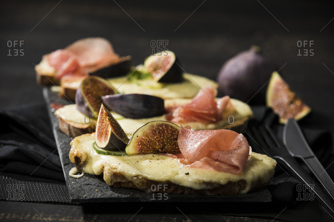 Close-up of baked cheese bread with fig and ham served on table
