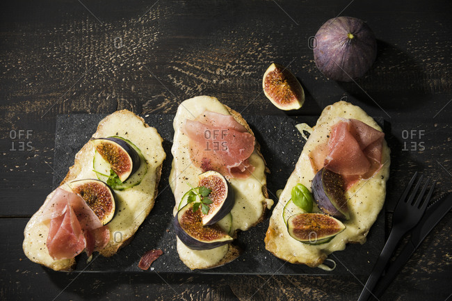 High angle view of baked cheese bread with fig slices and ham served on wooden table