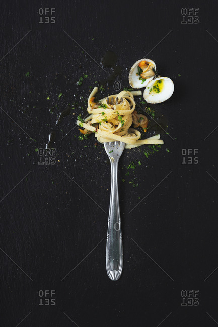 High angle view of clams and noodles in fork on black background