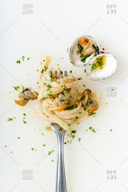 High angle view of clams and noodles in fork on white background