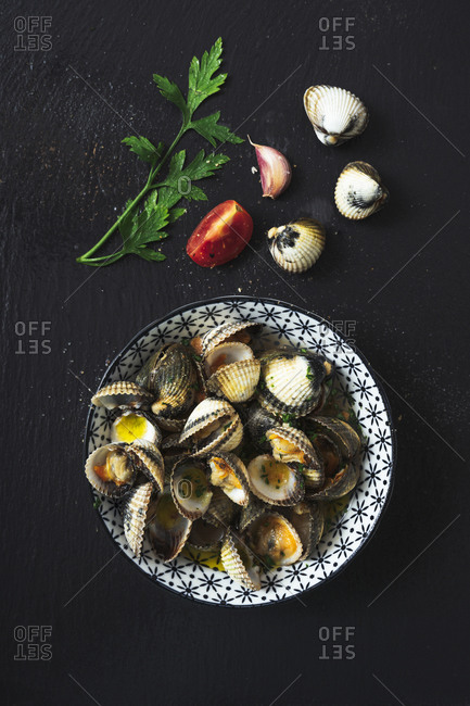 Directly above shot of clams in plate by ingredients on black background