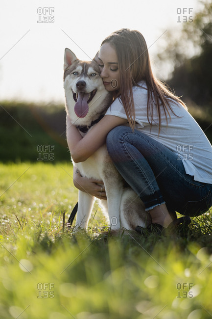 Young woman hugging her dog on a meadow