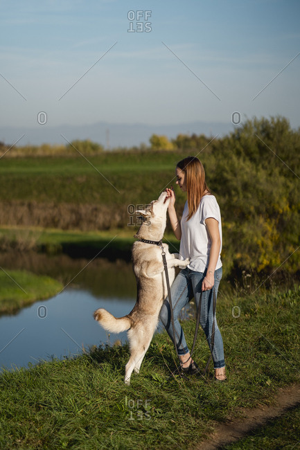 Young woman teaching her dog in nature