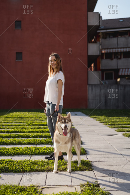 Portrait of happy young woman going walkies with her dog in the evening