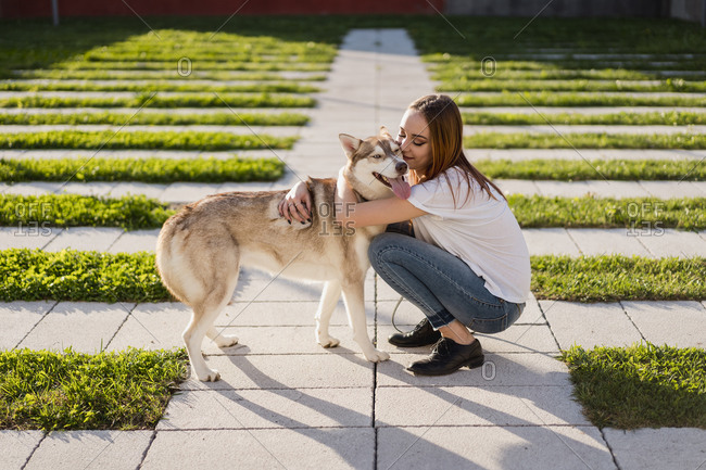 Happy young woman cuddling her dog outdoors
