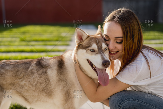 Happy young woman cuddling her dog