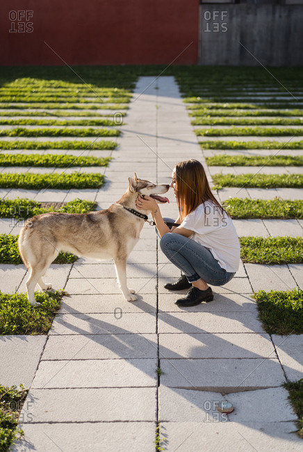 Young woman cuddling her dog outdoors