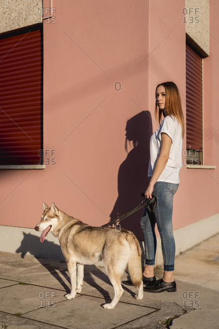 Portrait of young woman going walkies with her dog in the evening