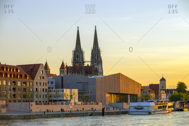 May 26, 2019: Saint Peter's Cathedral and Museum Brandhorst by Danube river against sky during sunset- Regensburg- Germany