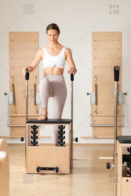 Pretty Caucasian woman doing pilates exercise using equipment.