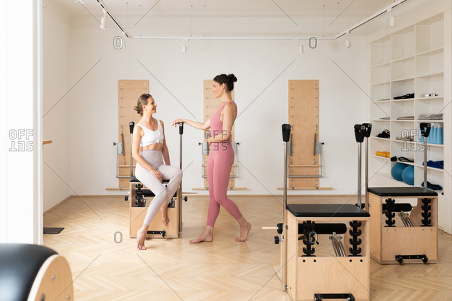 Two pretty smiling sportswomen chatting at pilates studio.