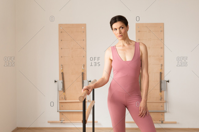 Portrait of beautiful woman holding ballet barre.