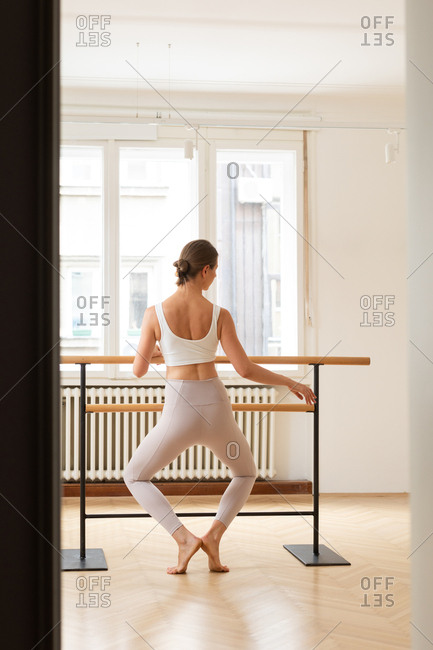 Back view of unrecognizable woman doing exercise on ballet barre.