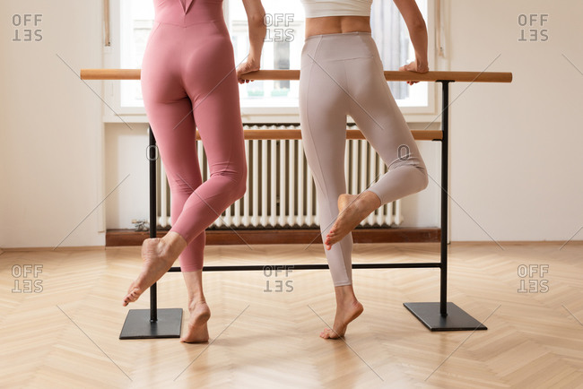 Legs of two ballet dancers doing barre exercise together at studio.
