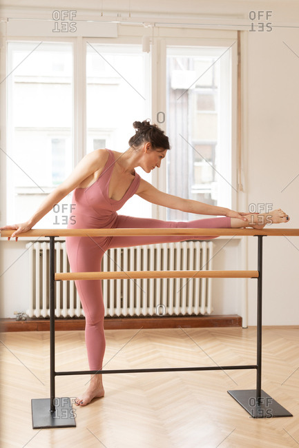Pretty Caucasian woman in pink sporty overalls doing ballet exercise on barre.