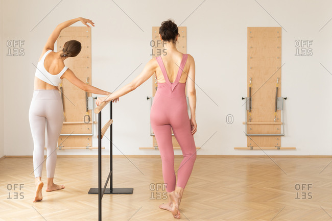 Two beautiful Caucasian women doing exercise on ballet barre.