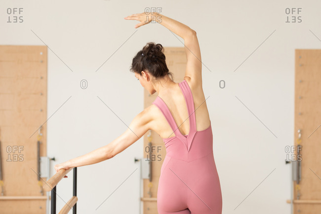 Back view of pretty Caucasian woman doing ballet exercise on barre.