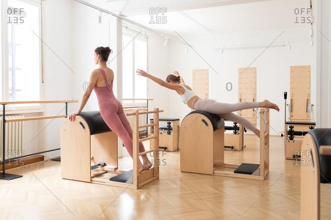 Two sportswomen doing together fitness exercise at pilates studio.