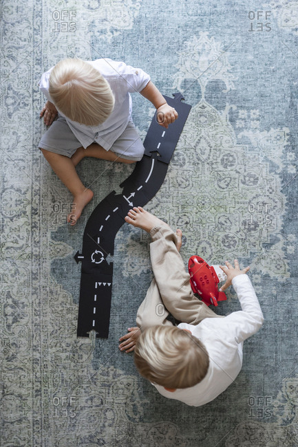 From above photo of little boys playing with cars and road toys on the floor.