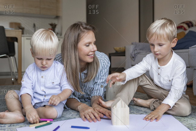Beautiful smiling woman playing at home with her kids.