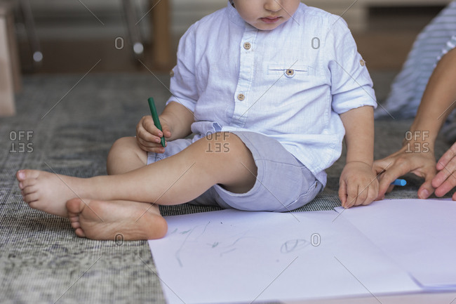 Little toddler boy drawing on the floor with his mom.