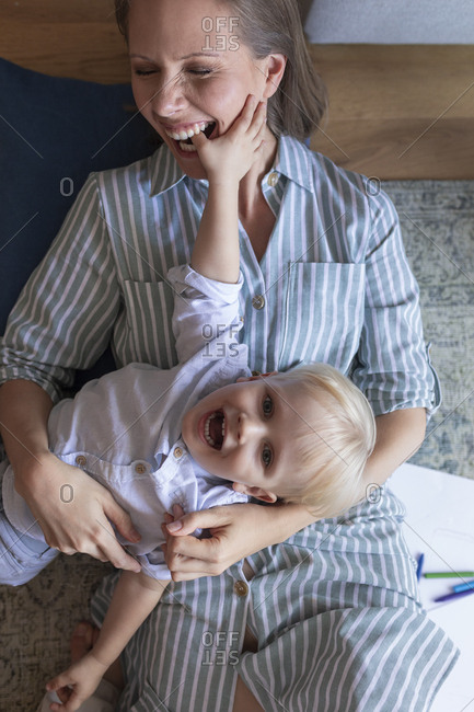 Portrait of smiling mother and a child having fun cuddling and playing.