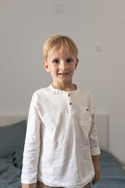 Portrait of cute blond Caucasian boy looking at camera.