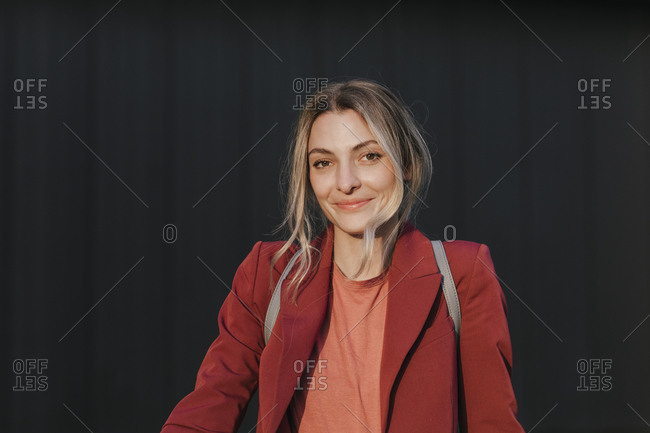 Portrait of young pretty Caucasian smiling businesswoman  with backpack looking at camera.