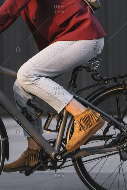 Legs of a woman in jeans riding a bike.