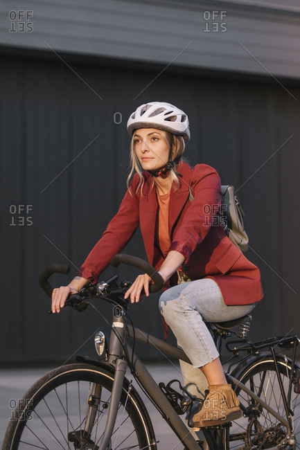 Young pretty businesswoman commuter riding a bike and wearing helmet.