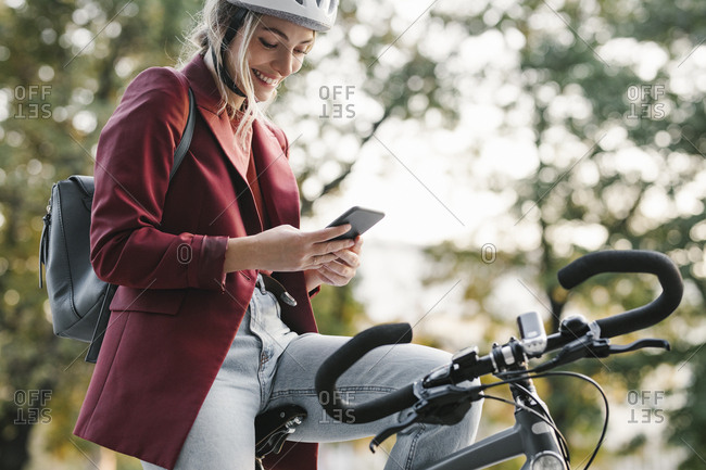 Beautiful young businesswoman with a helmet on her head sitting on a bicycle and typing on her cell phone.