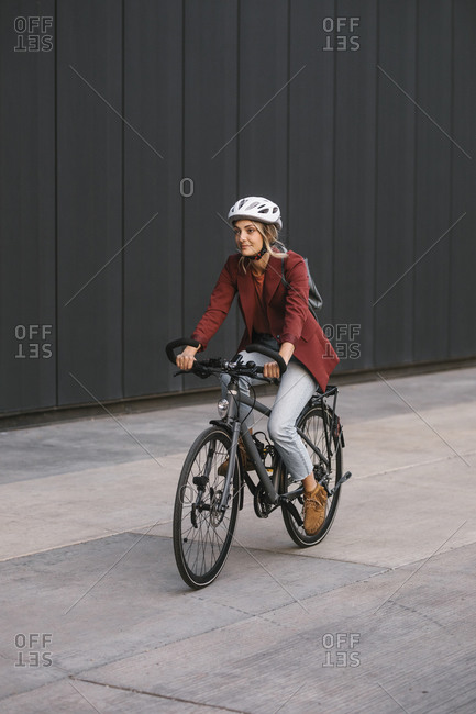 Young businesswoman commuter riding a bike.