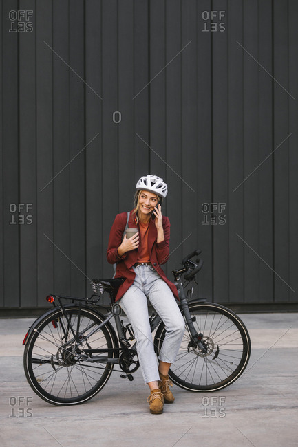 Pretty smiling young businesswoman sitting on her bike and talking on a cell phone.