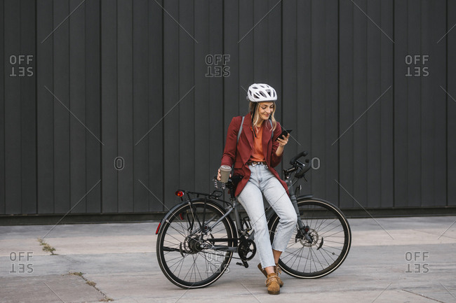 Pretty smiling young businesswoman sitting on her bike and typing on a cell phone.
