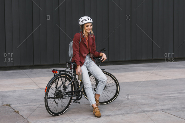 Portrait of beautiful young smiling businesswoman with helmet sitting on her bike.