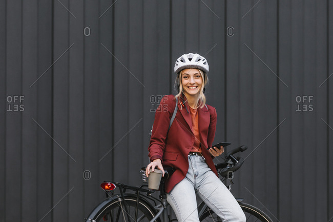 Portrait of beautiful young smiling businesswoman with helmet sitting on her bike and looking at camera.