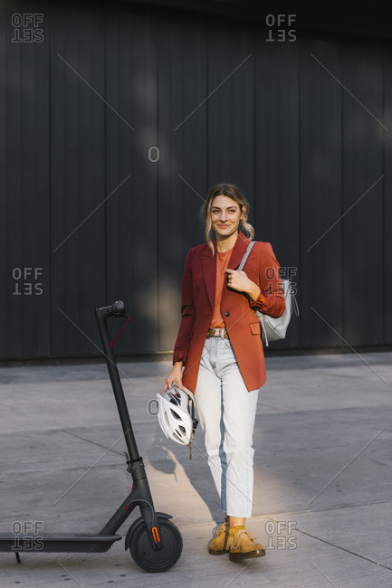 Portrait of young businesswoman holding a safety helmet for riding electrical scooter.