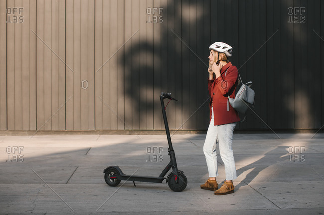 Young businesswoman putting a safety helmet on her head for riding electrical scooter.