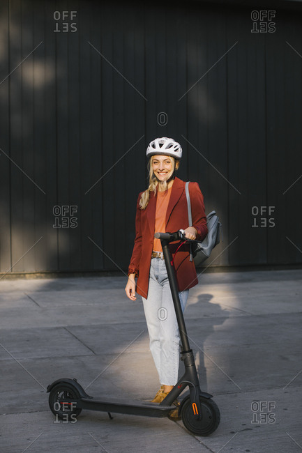 Portrait of beautiful smiling young woman with safety helmet for driving electrical scooter.