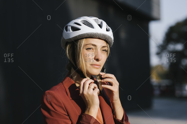 Young beautiful businesswoman putting safety helmet on her head for electrical scooter driving.